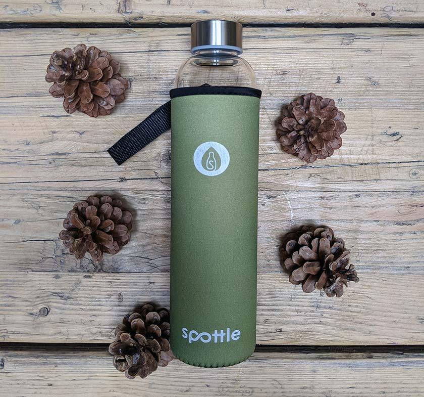 Spottle Glas-Trinkflasche 750ml mit grüner Neoprenhülle auf einem Holztisch
