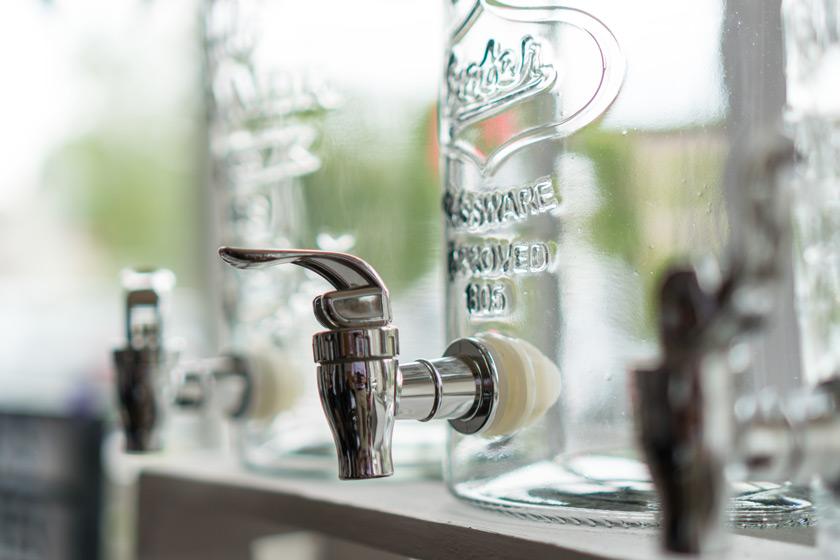 Wasserspender aus Glas im Detail mit Edelstahl-Hahn
