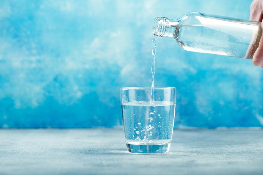 Glas und Glasflasche vor blauem Hintergrund