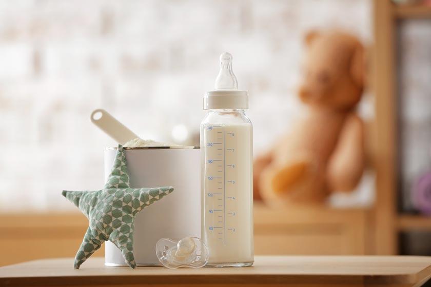 Babyflasche aus Glas neben Topf und Stoffstern
