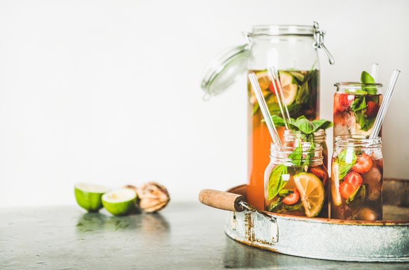 Bunte Frucht-Cocktails in Karaffen und Gläsern mit Glas-Strohhalmen