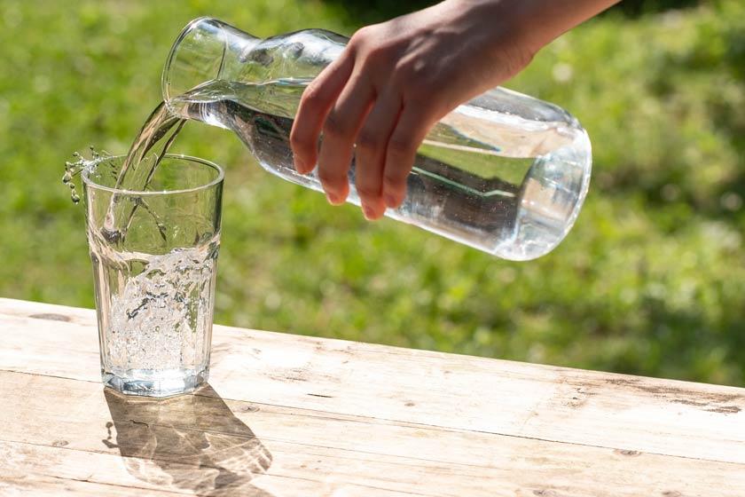 Hand gießt mit Wasserkaraffe Wasser in ein Glas